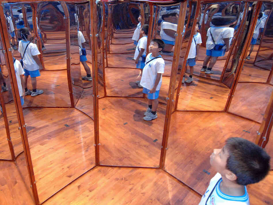 A boy looks at his reflections in angled m