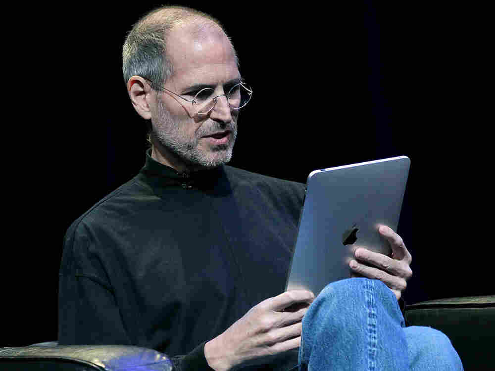 Apple CEO Steve Jobs sits with the new iPad in his lap at the Yerba Buena Center for the Arts on Jan