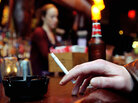 a closeup of a man's hand holding a cigarette in a New York bar.
