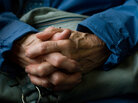 An old person folds hands.
