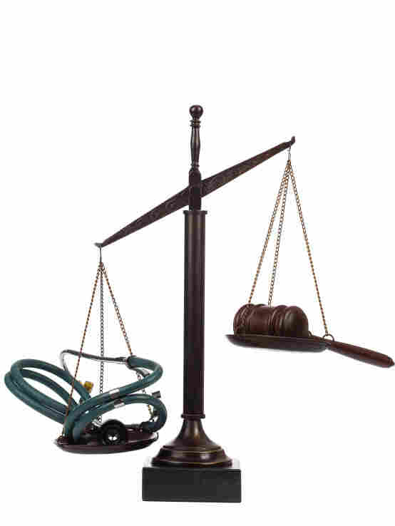 Scales holding a stethoscope in one side and a gavel in the other.