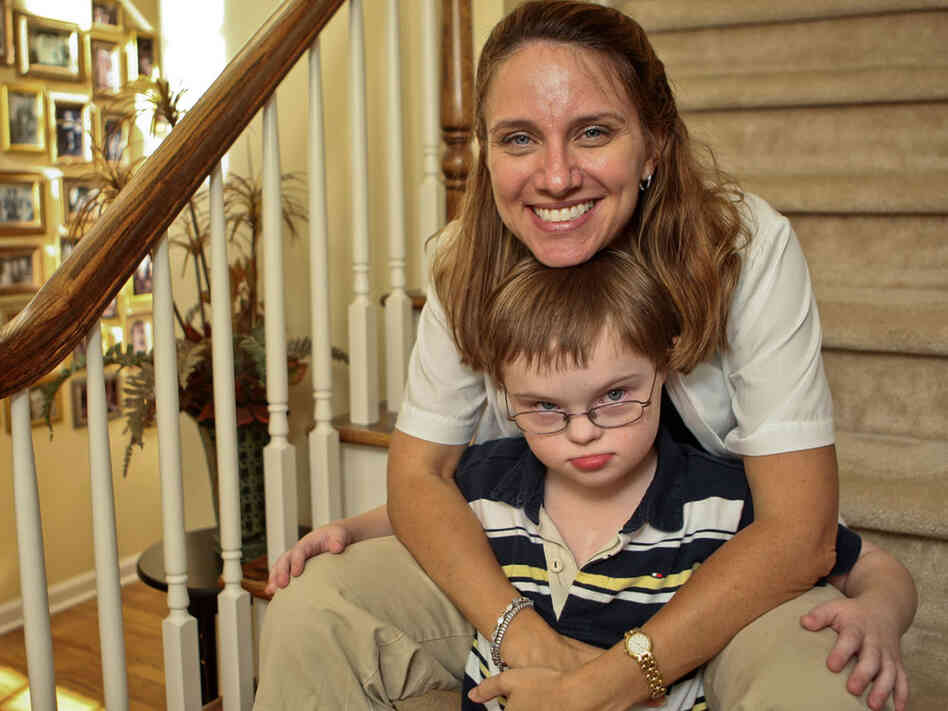 A mother holds her son who has Down Syndrome.