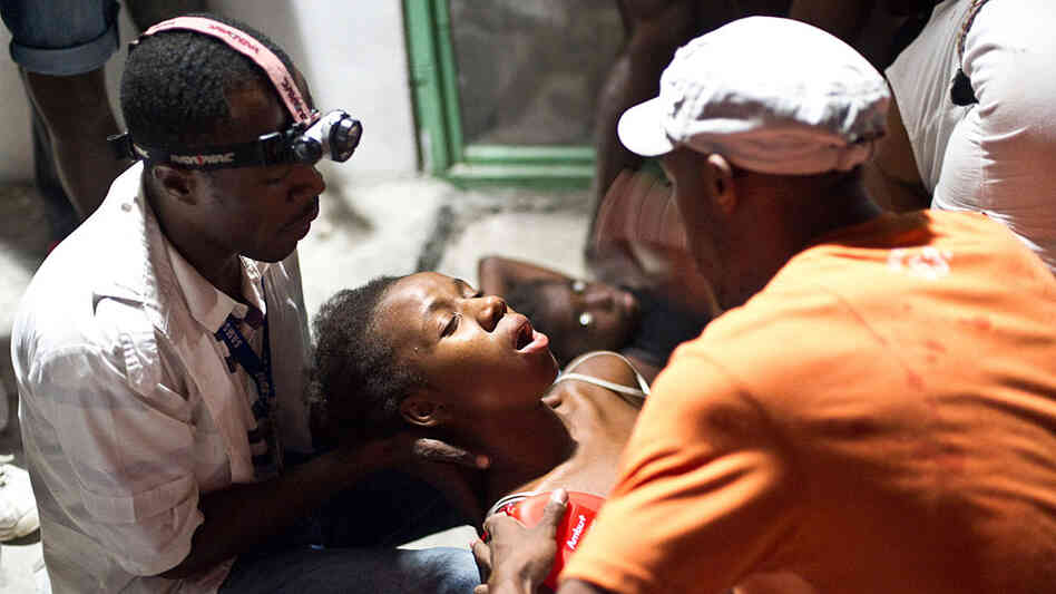 A woman faints in the arms of a medic in an emergency clinic in Petionville on January 12, 2010 in P