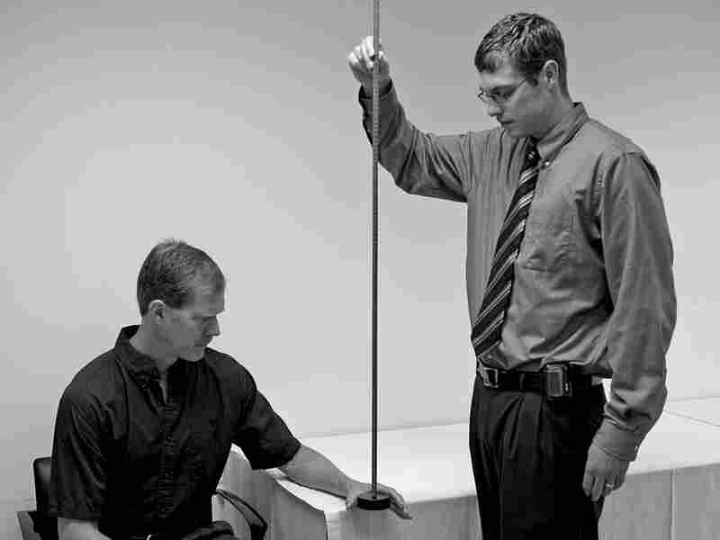 A researcher tests a subject's reaction time by having him catch a weighted stick.
