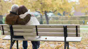 Older couple sitting on park bench.