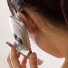 Woman holds cellphone close to her ear.