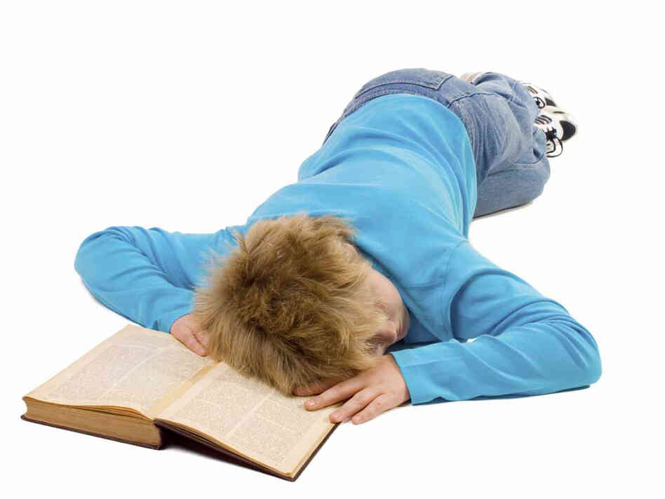 Teen boy sleeping on a book.
