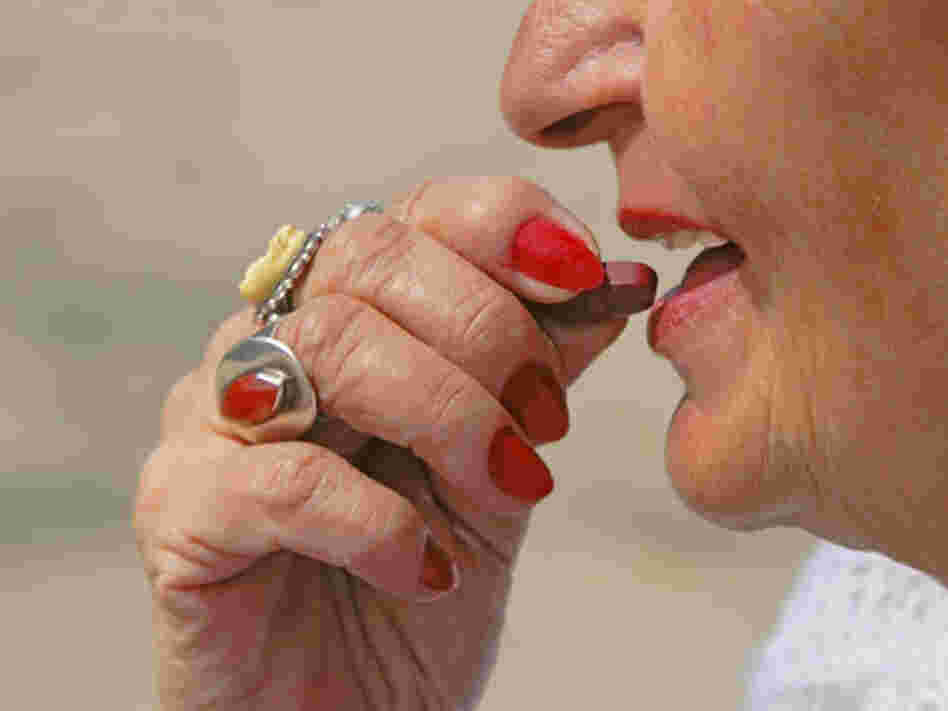 Older woman puts vitamin tablet in her mouth.