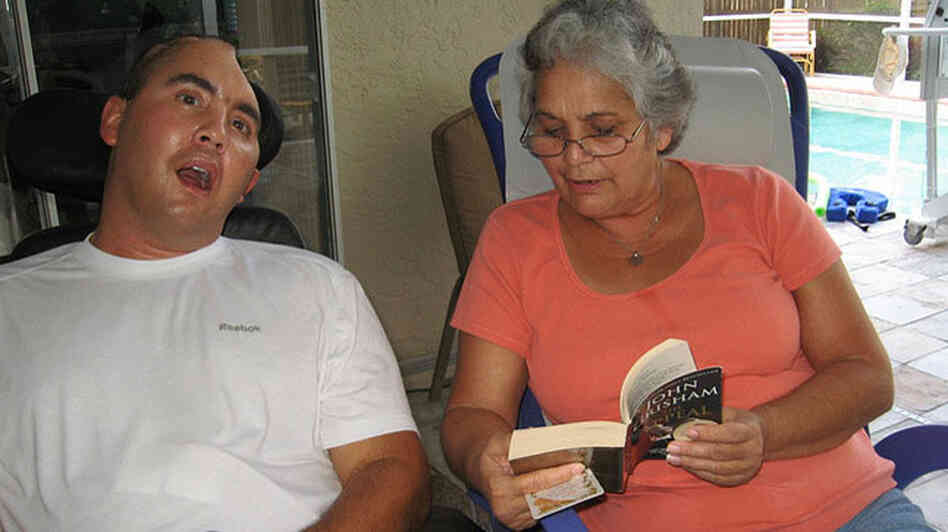 Nellie Bagley reads to her son Jose Pequeno at their Tampa home. Credit: Daniel Zwerdling, NPR.