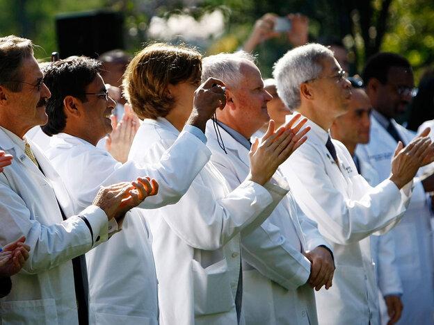 Doctors applaud President Obama.