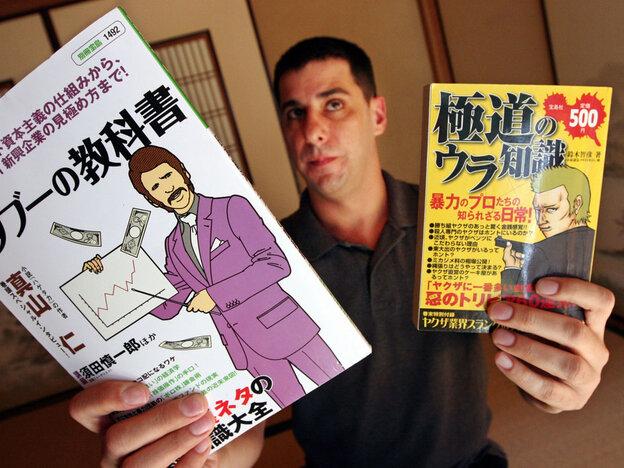 Jake Adelstein holds up manga magazines based on the yakuza
