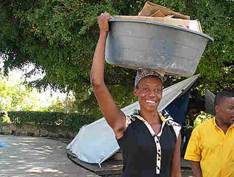 A woman carries a large bucket of goods on her head in Haiti.