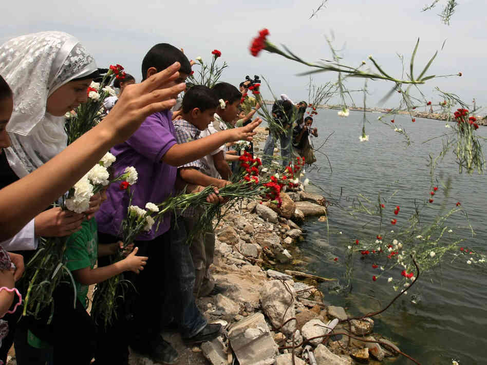 Palestinian children throw flowers in memory of the activists killed in a deadly Israeli raid.