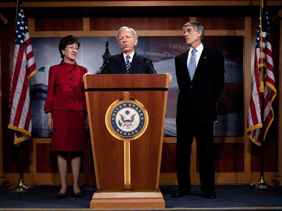 Sen. Susan Collins (R-ME) (L) and Sen. Mark Udall (D-CO) (R) listen to Sen. Joseph Lieberman (I-CT) speak.