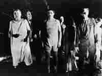 A line of undead 'zombies' walk through a field in the night in a still from the film, 'Night Of The
