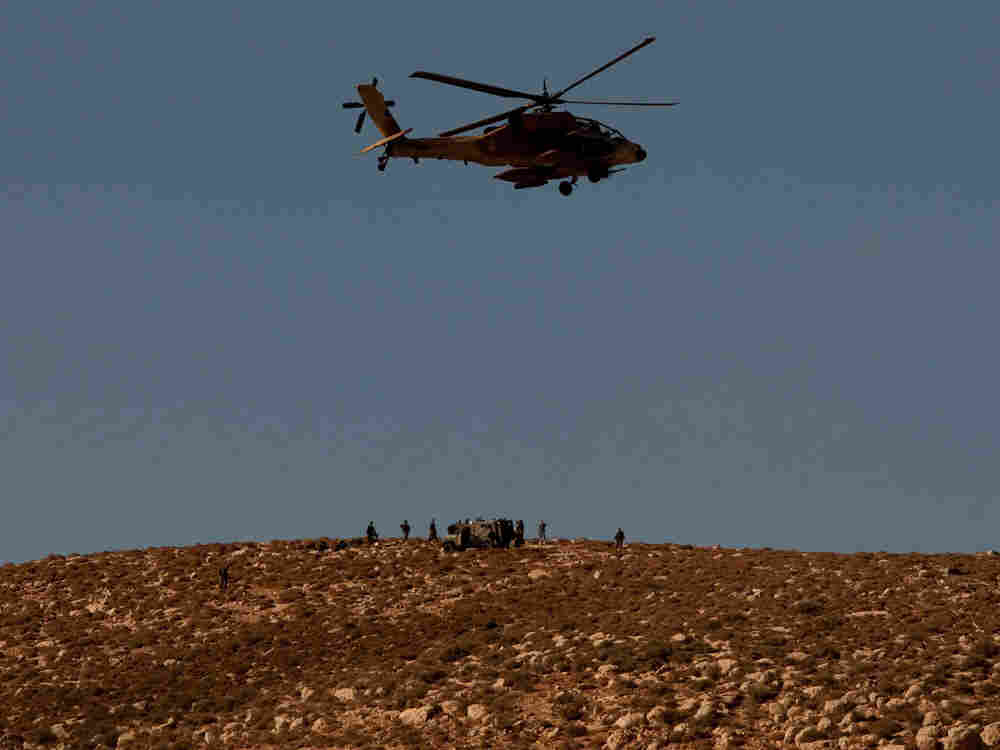 An Israeli air force combat helicopter flies over the crash site of a F-16 warplane that was flown b