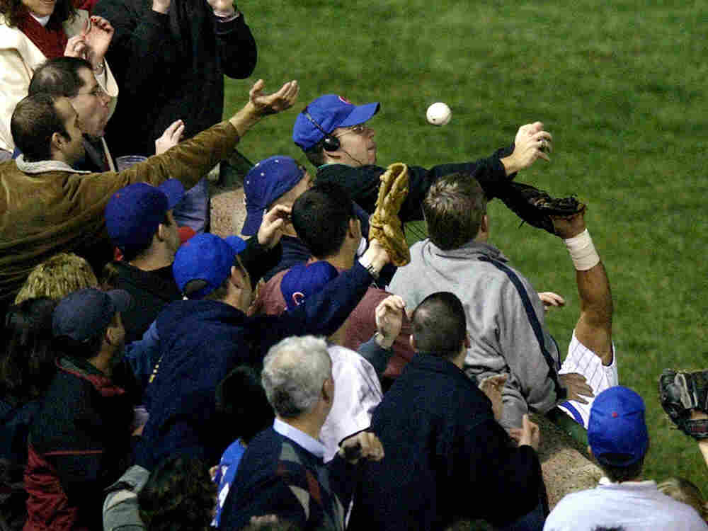 In this Oct. 14, 2003 file photo, Chicago Cubs left fielder Moises Alou's arm is seen reaching into