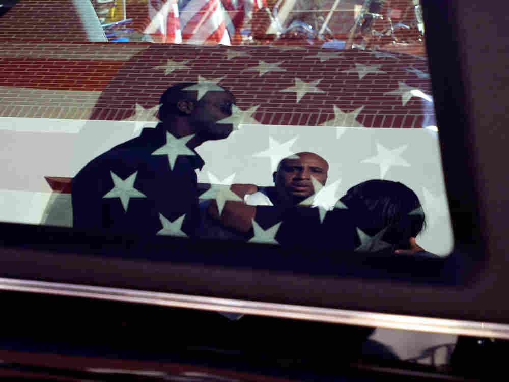 Friends and family members watch the casket of Staff Sgt. Vernon Martin being loaded into a hearse o