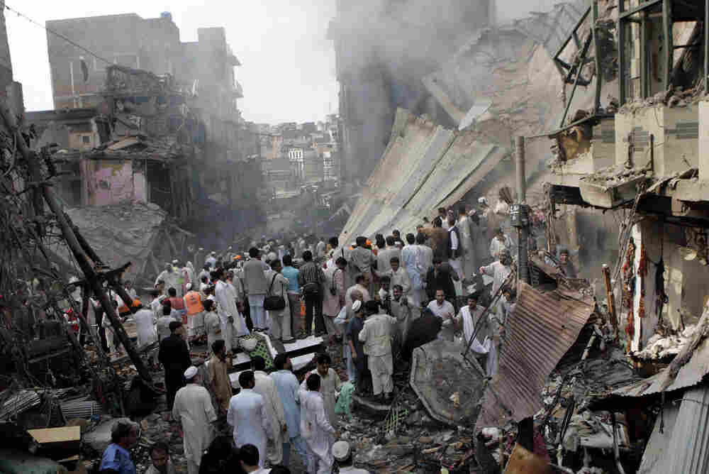 People gather at the site of an explosion in Peshawar, Pakistan on Wednesday Oct. 28, 2009. A car bo