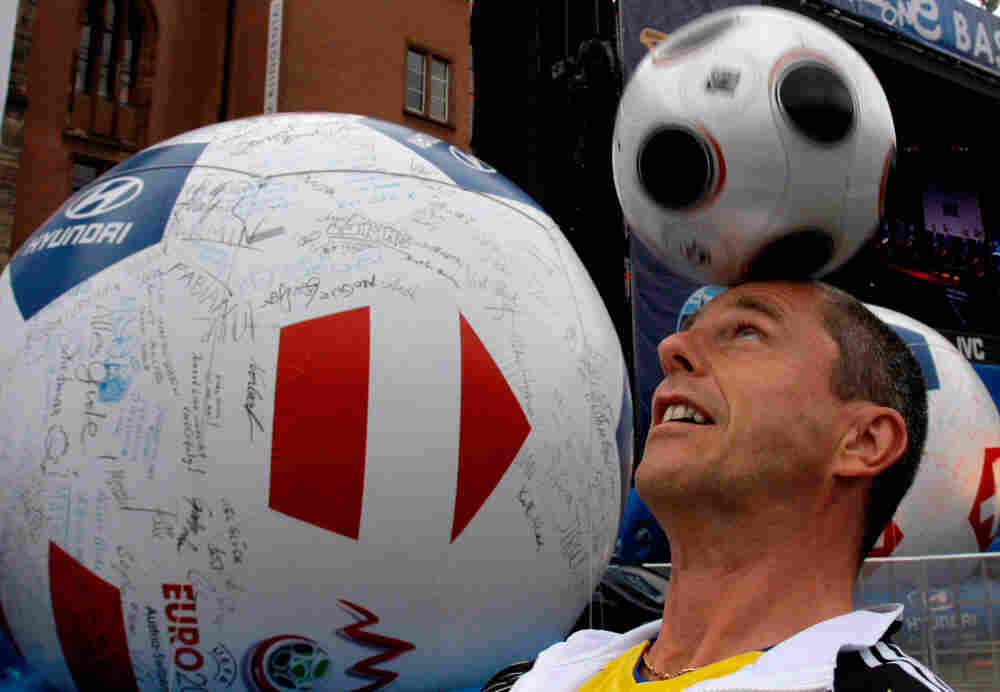 A man heads a ball as he plays next to a blown up ball bearing signatures, in the fan zone in downto