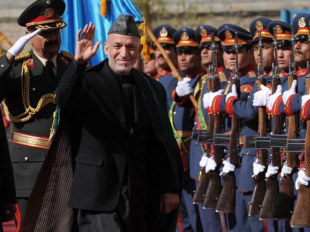 Afghan President Hamid Karzai passes an honor guard as he arrives for his swearing in ceremony as th