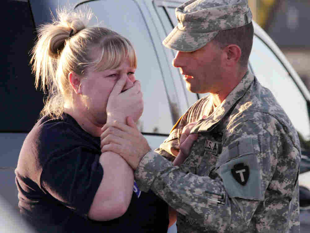 Sgt. Anthony Sills, right, comforts his wife as they wait outside the Fort Hood Army Base near Kille
