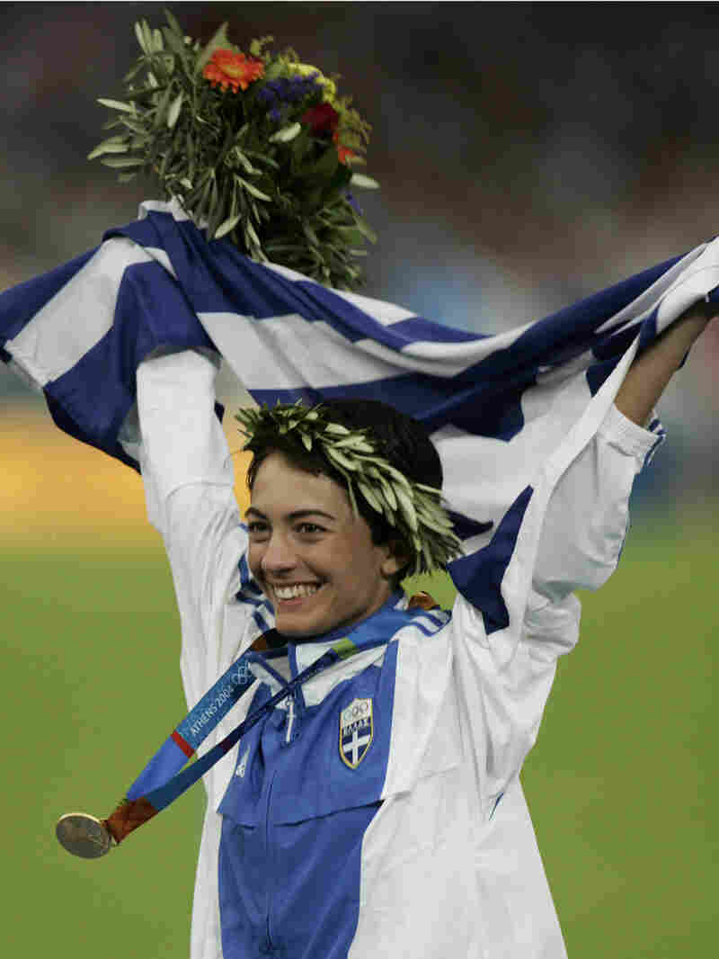 Greece's Athanasia Tsoumeleka, waves her national flag, after being presented with the gold medal fo