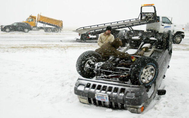 Brent Levander watches as his brother, Brian, hooks a chain to the bottom of a vehicle as they work