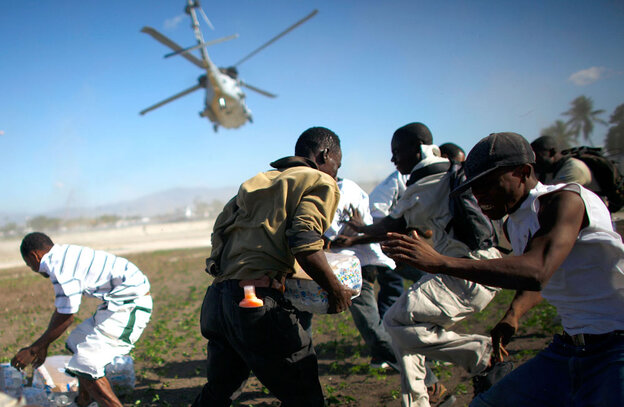 Men scramble Saturday to grab some of the relief supplies delivered by a U.S. military helicopter. (