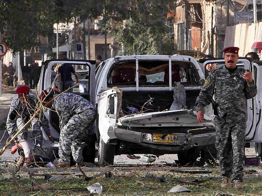 Iraqi police evacuate a victim of a bomb attack in Baghdad, Iraq, Monday, Jan. 25, 2010. Three large
