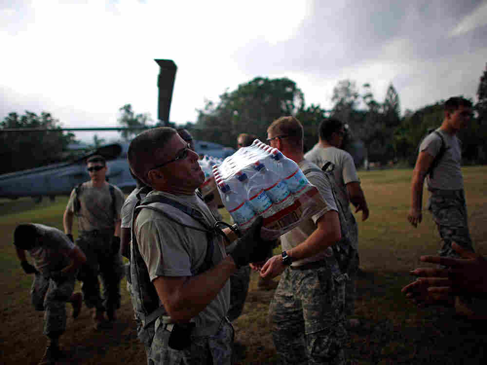 U.S. Army soldiers from the 82nd Airborne pass relief from a Navy helicopter supplies at a golf club