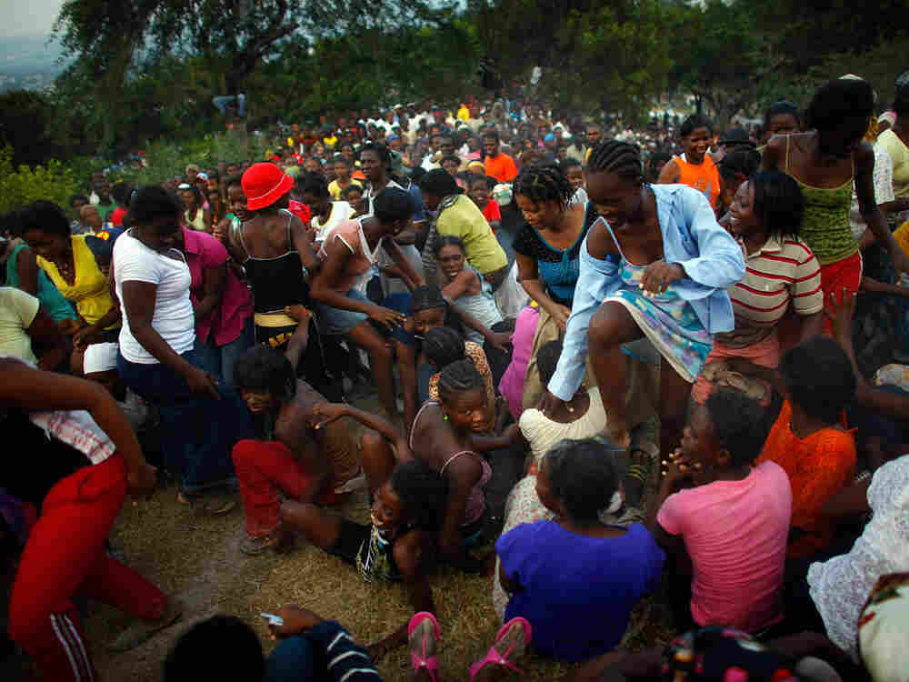 Haitian women surge forward on a hill to try and get the last handouts of food rations at distributi