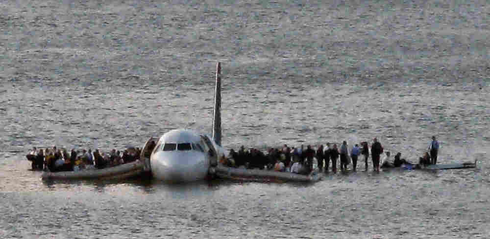 In this file photo from Jan. 15, 2009, airline passengers wait to be rescued on the wings of a US Ai
