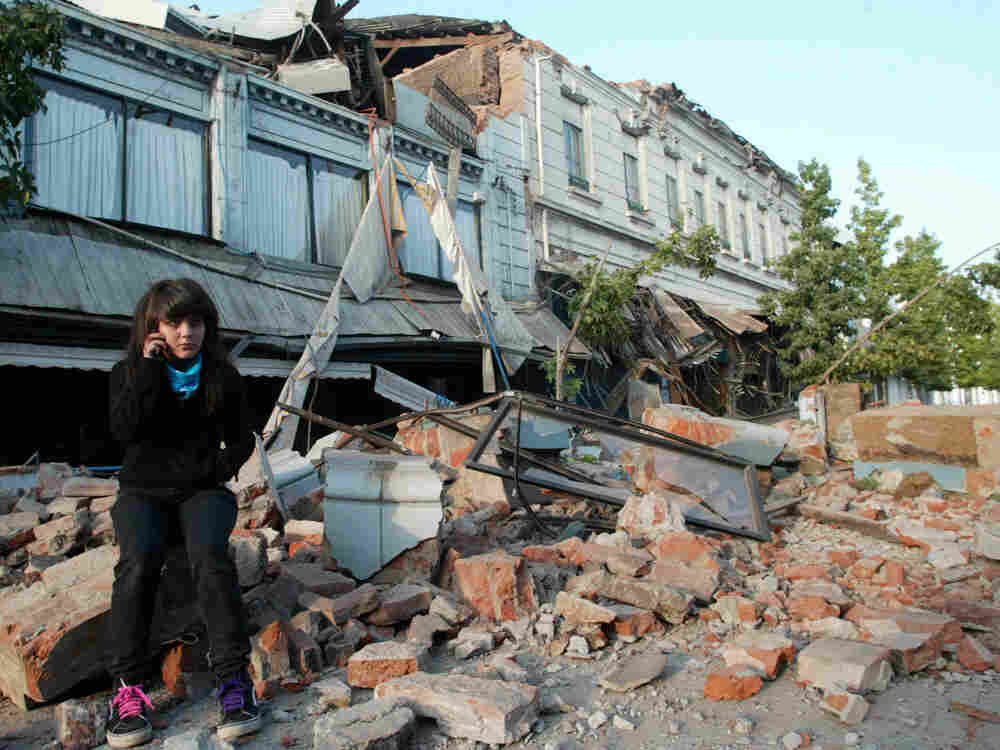 A resident sits on the debris of a collapsed house in the city of Talca, some 275 kilometers south o
