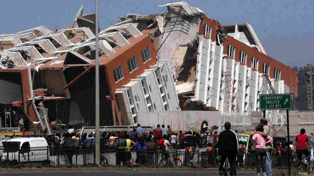 Residents look at a collapsed building in Concepcion, Chile, Saturday Feb. 27, 2010, (AP Photo)