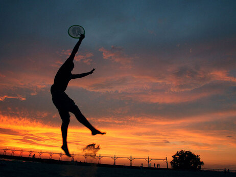 2007 file photo: James Mitterling of Lansing, Mich., leaps from the sand of South Haven's South Beach to catch a frisbee as the sun sets in South Haven, Mich. (AP photo/Kalamazoo Gazette, Jonathon Gruenke)
