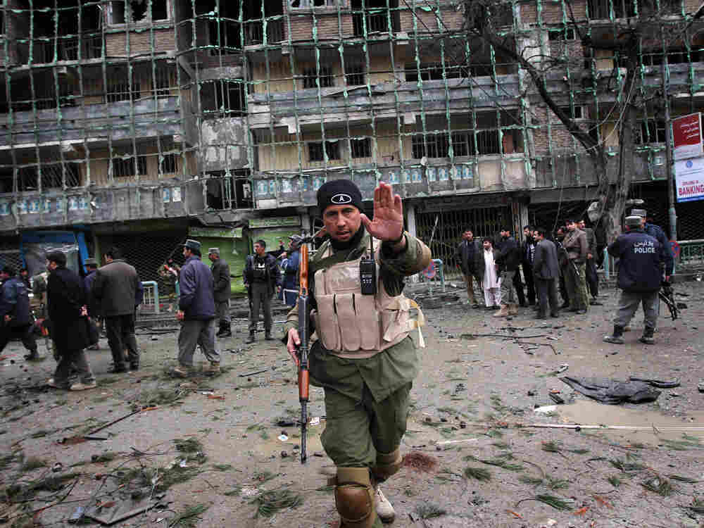 An Afghan security officer tries to keep photographers back from the scene outside the Park Residenc