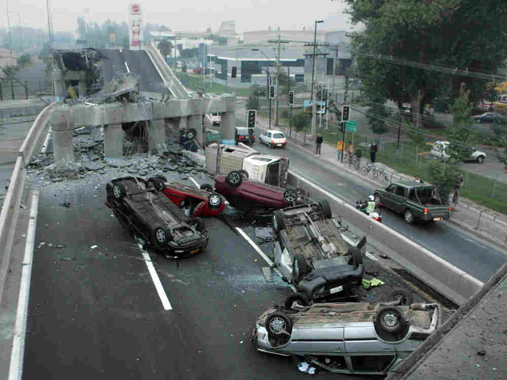 Vehicles that were driving along a highway that collapsed during the earthquake near Santiago are se