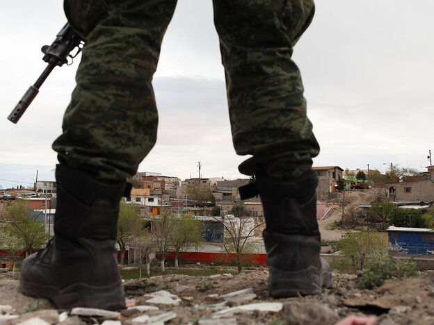A military police officer stands guard at the scene of a murder on March 23, 2010 in Juarez, Mexico.