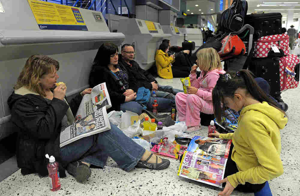 A family sits on the floor as they wait for flights at Manchester Airport in north-west England on A