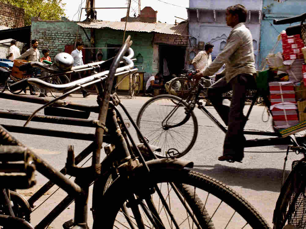 Iron bikes, which fill Indian roads, stand for sale as traffic rolls by a busy street in Aligarh. (K