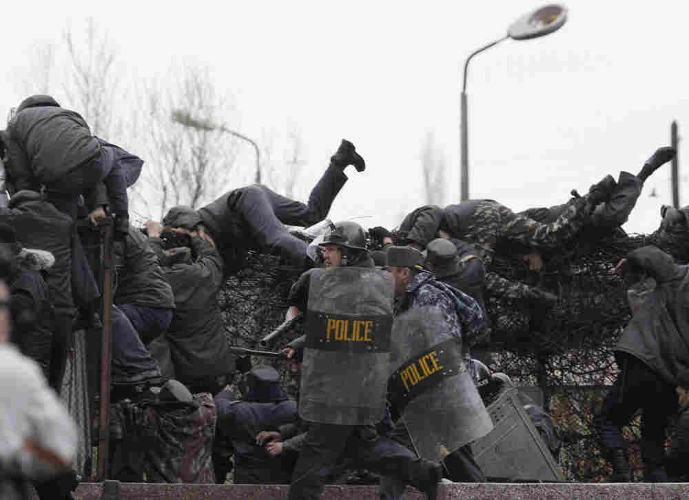 Kyrgyz police officers throw themselves over a wall as they flee from angry protesters, in Bishkek,