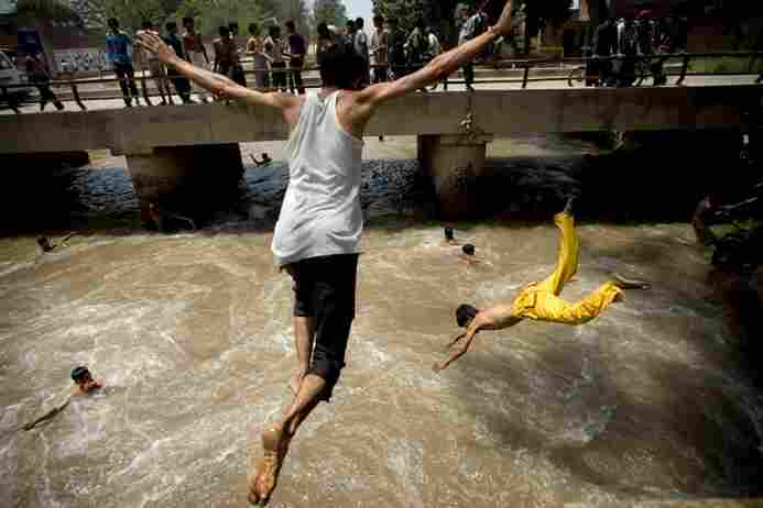 Pakistani men jump into a water canal to take a reprieve from the heat in Lahore, Pakistan, on Sunda