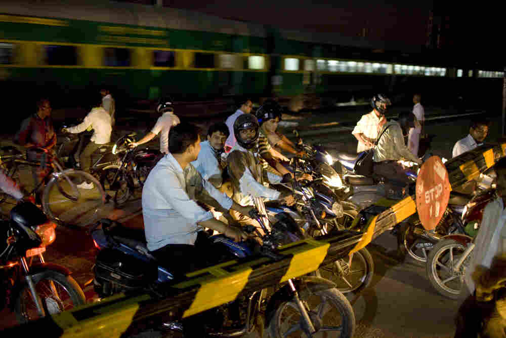 Just outside Noida at a busy railroad crossing, impatient motorists and bicyclists stand inches away