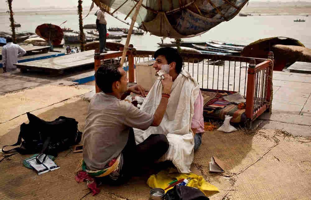 Barber Mahendra Singh shaves NPR's Nishant Dahiya on the banks of the Ganges River in Varanasi, Indi