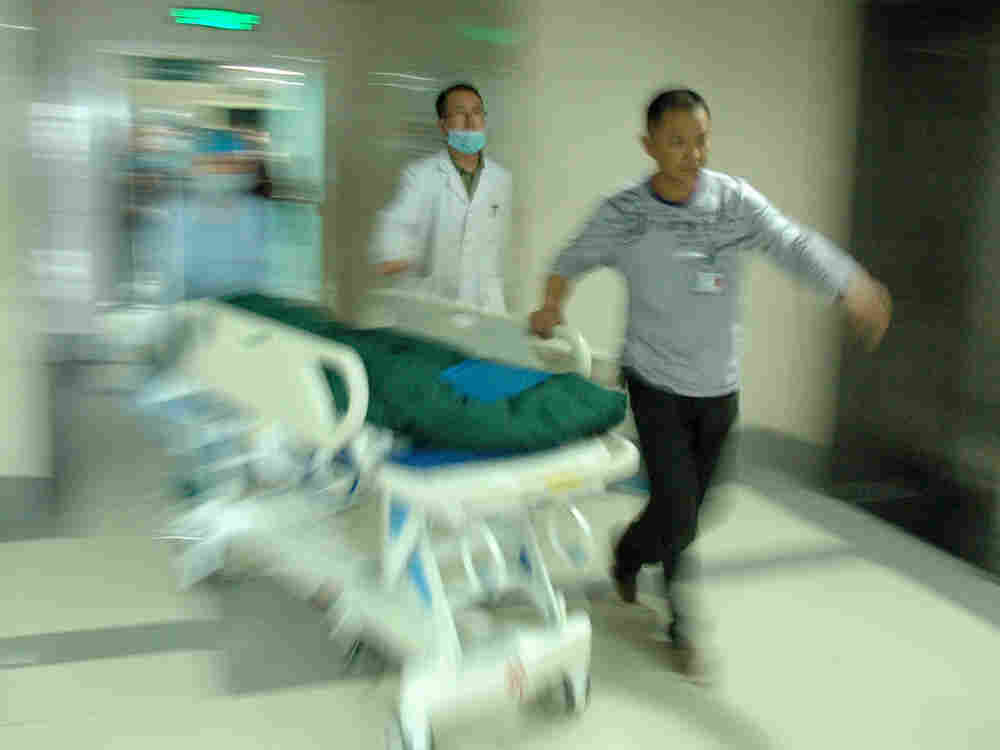 In this photo released by China's Xinhua News Agency, medical workers take an injured child to ICU a