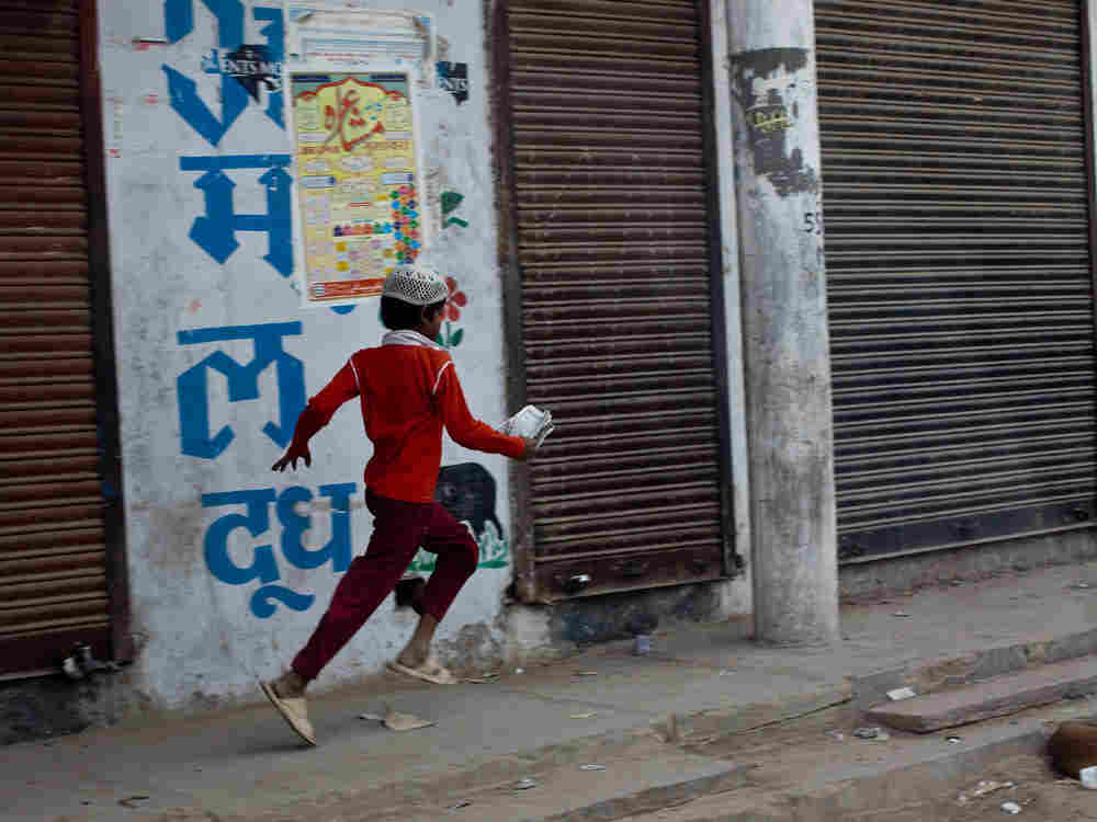 A young boy runs past a leather factory in Kanpur, India. (Photo by Kainaz Amaria for NPR)