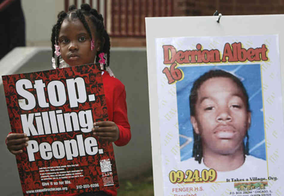 Nadashia Thomas, 6, a cousin of Derrion Albert, holds a sign beside a poster of Derrion Albert at Fe