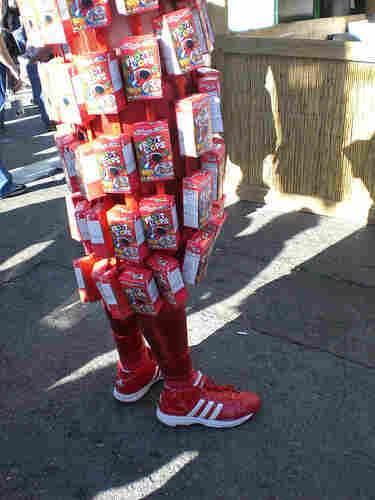 Man with boxes of Fruit Loops attached to his clothes.