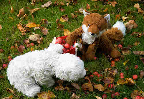 Photo of two toy animals reaching into basket of apples.